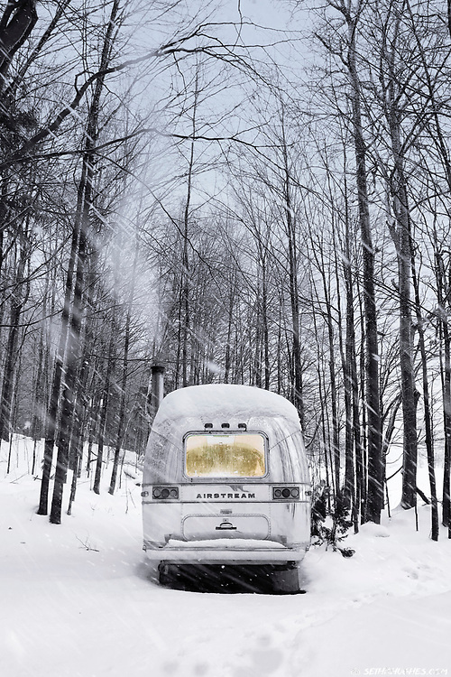 An Airstream trailer parked in the trees during a winter snow storm.