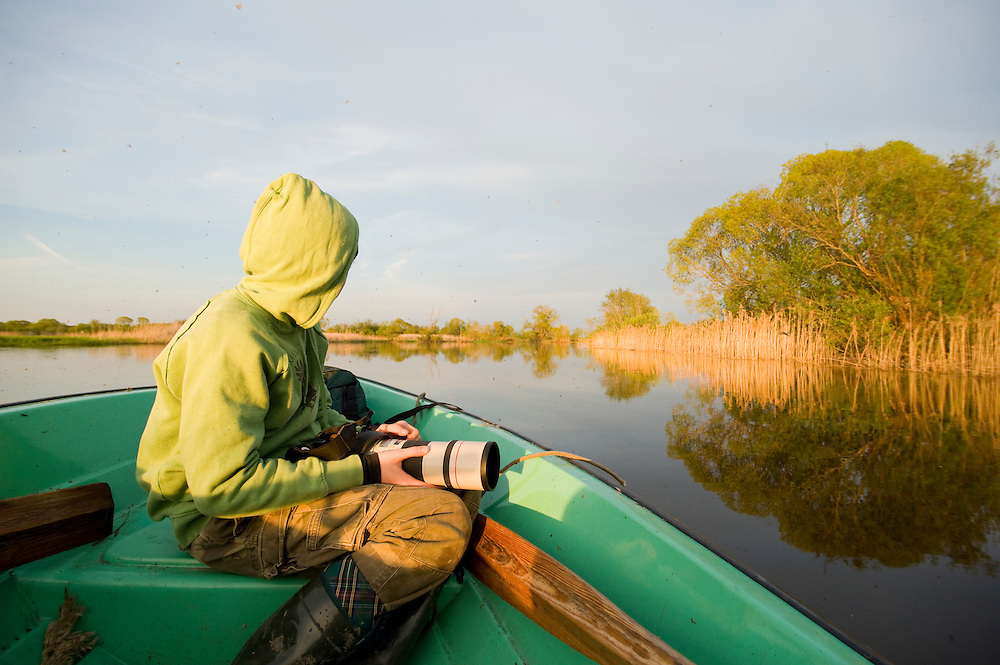 Young boy photographing from a boat on the Suur Emajogi, Estonia