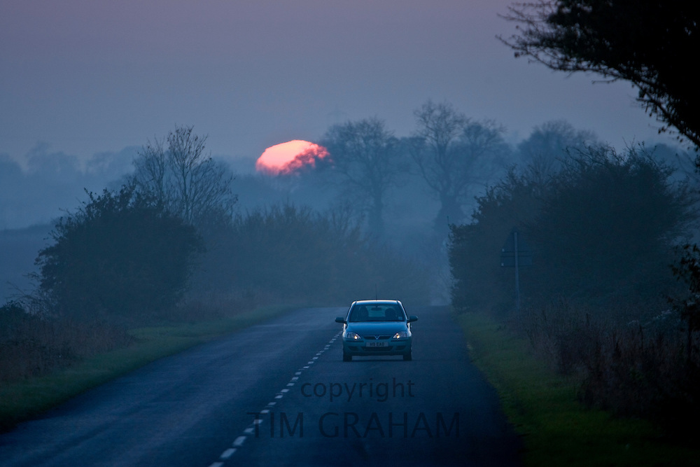 Car drives along a country road, Swinbrook, Oxfordshire,  UK