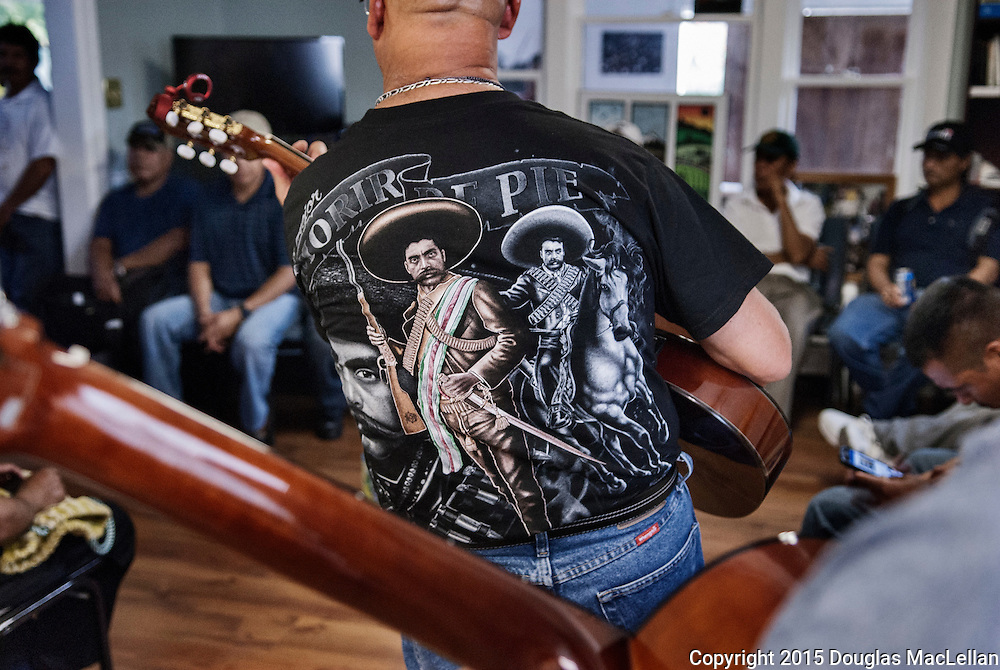 Eduardo Sanchez, not a migrant worker but rather a Leamington resident, plays guitar for a group of migrant workers at a workers's support centre. The Agricultural Workers Alliance organized a well attended barbecue for the mainly Spanish speaking workers.