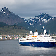 An Antarctic cruise ship, the Sea Adventurer opereated by Quark Expeditions, gets underway in Ushuaia Port, Argentina, with the mountains in the background. The distinctive, sharp triangle-shaped mountain is Monte Olivia (Mount Olivia).