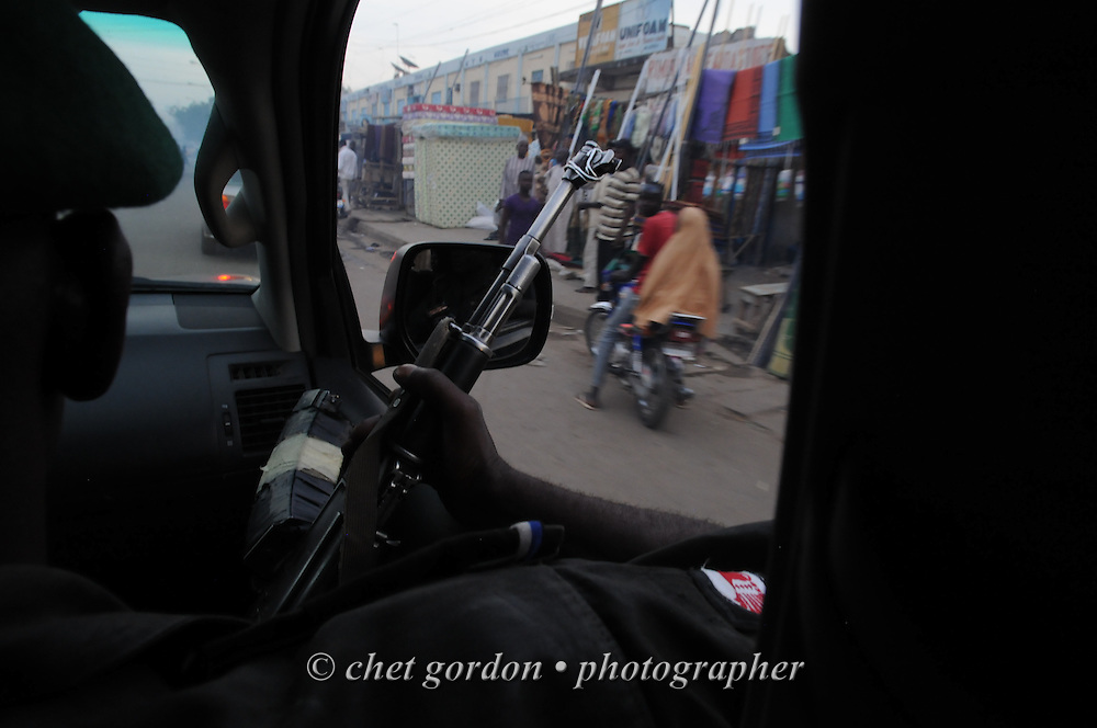 A Nigerian policeman rides in the backseat of an escort vehicle in Kano, Nigeria on Monday, December 3, 2012. A police officer directing traffic was killed the same day when a roadside bomb exploded near his intersection in Kano.  bomb exploded near his intersection in Kano.    © www.chetgordon.com