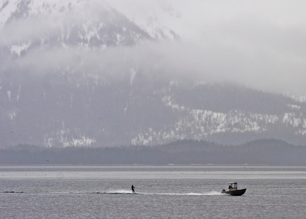 When the fishing season is over, fisherman find diversion by using the skiff for water skiing in wet suits in Icy Strait, Southeast Alaska.