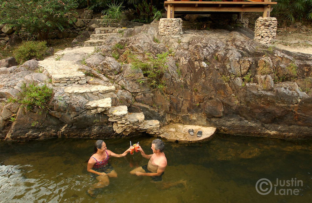 Chris Tompson (R) and Toni Cervantes, of Los Angeles, CA, relax in the river that runs through the Blancaneaux Lodge, of Francis Ford Coppola's resorts, in the eastern part of Belize.<br />