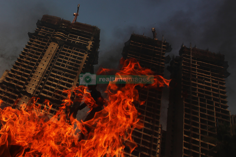 April 28, 2019 - Mumbai, India - A boy is silhouetted as he stands behind burning tyres put up on fire in Mumbai, India on 28 April 2019. Climate change has featured for the first time in the manifestoes of India's two major political parties, the Indian National Congress (INC) and Bharatiya Janta Party (BJP) in the 2019 general election as per media report. (Credit Image: © Himanshu Bhatt/NurPhoto via ZUMA Press)