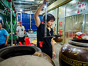 "14 FEBRUARY 2019 - SIHANOUKVILLE, CAMBODIA:  A Chinese woman who operates a Chinese restaurant with her husband checks on soups she bakes in a clay jar. There are thousands of Chinese workers in Sihanoukville who work to support the casino and hotel industry in the town and thousands of other Chinese migrants have moved into Sihanoukville and opened businesses that cater to the workers. There are about 80 Chinese casinos and resort hotels open in Sihanoukville and dozens more under construction. The casinos are changing the city, once a sleepy port on Southeast Asia's ""backpacker trail"" into a booming city. The change is coming with a cost though. Many Cambodian residents of Sihanoukville  have lost their homes to make way for the casinos and the jobs are going to Chinese workers, brought in to build casinos and work in the casinos.     PHOTO BY JACK KURTZ"