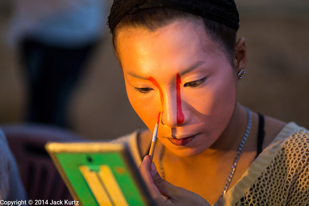 "28 JANUARY 2014 - BANGKOK, THAILAND: A performer with the Tear Kia Ee Lye Heng opera troupe puts on her makeup before a show. They were performing for a business in the Min Buri district of Bangkok for the Lunar New Year, which this year is Jan 31. Chinese opera was once very popular in Thailand, where it is called ""Ngiew."" It is usually performed in the Teochew language. Millions of Teochew speaking Chinese emigrated to Thailand (then Siam) in the 18th and 19th centuries and brought their cultural practices with them. Recently the popularity of ngiew has faded as people turn to performances of opera on DVD or movies. There are still as many 30 Chinese opera troupes left in Bangkok and its environs. They are especially busy during Chinese New Year when they travel from Chinese temple to Chinese temple performing on stages they put up in streets near the temple, sometimes sleeping on hammocks they sling under their stage. They are also frequently hired by Chinese owned businesses to perform as a form of merit making.    PHOTO BY JACK KURTZ"