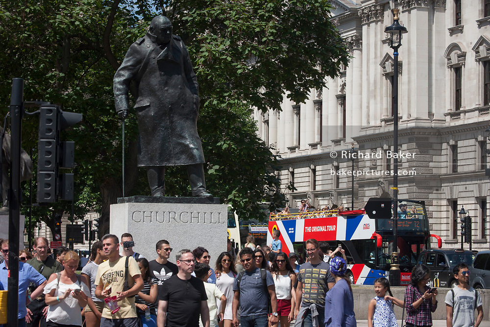 A tour bus with The Original Tour drives past the statue of wartime Prime Minister Winston Churchill on its route through Parliament Square, on 7th July 2017, in central London.