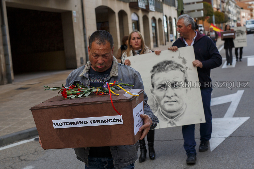 14/04/2018. Supporters hold a coffin containing the remains of victims of Spain Civil War Victoriano Tarancon and a portrait depicting him along the streets in center of Soria during a homage to hand the remains to their families on April 14, 2018 in Soria, Spain. La Asociacion Soriana Recuerdo y Dignidad (ASRD) 'The Soria Association for Memory and Dignity' celebrated a tribute to hand over the remains of civil war victims to their families. The Society of Sciences of ARANZADI helped with the research, exhumation and identification of the bodies, after villagers passed the information about the mass grave, 81 years after the assassination took place, to the ASRD. Seven people were assassinated around August 25, 1936 by Falangists, as part of General Francisco Franco armed forces, and buried in the 'Fosa de los Maestros' (Teachers Mass Grave) near Cobertelada, Soria, after being taken from prison of Almazan during the Spanish Civil War. Five of them were teachers in the region, and also friends of Spanish writer Antonio Machado. The other two still remain unidentified. Another body was assassinated by Falangists accompanied by a priest in 1936, and was exhumed on 23 September of 2017 near Calata&ntilde;azor, Soria. It belonged to Abundio Andaluz, a politician, lawyer and musician in Soria.<br /> Spain's Civil War took the lives of thousands of people on both sides, and civilians. But Franco continued his executions after the war has finished. Teachers, as part of the education sector, were often a target of Franco's forces. Spanish governments has never done anything to help the victims of the Civil War and Franco's dictatorship while there are still thousands of people missing in mass graves around the country. (&copy; Pablo Blazquez)
