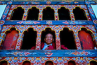 Monk looking out ornate window, near Lumitsawa, Punakha Valley, Bhutan