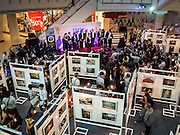 "19 JULY 2013 - BANGKOK, THAILAND:   People walk through the photo exhibit while the Yale Whiffenpoofs, one of the best-known collegiate a cappella groups in the world perform in CentralWorld in Bangkok Friday. Founded in 1909, the ""Whiffs"" began as a senior quartet that met for weekly concerts at Mory's Temple Bar, the famous Yale tavern. The Bangkok stop was a part of their 2013 world tour and was sponsored by the US Embassy. They sang at the opening of a photo exhibit that marked 180 years of friendly diplomatic relations between Thailand and the United States.   PHOTO BY JACK KURTZ"