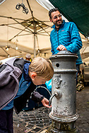 """A child drinks from a """"nasone,"""" one of Rome's public drinking fountains on a family vacation in Rome. His dad stands nearby at Campo de Fiori Market. Model released."""