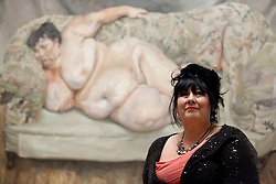 © Licensed to London News Pictures. 08/02/2012. LONDON, UK. .Sue Tilly poses in front of Lucian Frued's 'Benefits Supervisor Sleeping' a portrait of her on display at the National Portrait Gallery. .The exhibition entitled Lucian Frued Portraits, due to open on the 9th of February 2012, represents one of the largest collections the late artists work ever assembled with over 100 paintings, drawings and etchings on display. Photo credit: Matt Cetti-Roberts/LNP