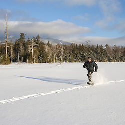 Snowshoeing across Little Lyford Pond in Maine's Northern Forest.  Near Greenville.  Baker Mountain is in the distance.