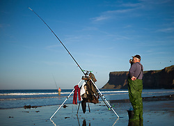 © Licensed to London News Pictures. <br /> 12/10/2014. <br /> <br /> Saltburn, United Kingdom<br /> <br /> A fisherman grabs a quick brew as he takes part in the annual Jim Maidens memorial beach fishing competition in Saltburn by the Sea in Cleveland. <br /> The competition is held each year to mark the death of Saltburn plumber and keen fisherman Jim Maidens who died in 1998 when he was killed after being swept overboard from his boat 'Corina' close to the beach at Saltburn.<br /> <br /> Photo credit : Ian Forsyth/LNP
