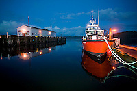 A Coast Guard vessel tied up at the Government Wharf in Hardy Bay reflects the final light of the day.  Port Hardy, Vancouver Island, British Columbia, Canada.