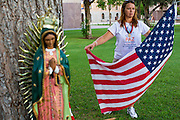 "19 JULY 2012 - PHOENIX, AZ:  MARIA URIBE unfurls an American flag at the Arizona Capitol during a vigil the first day of a class action lawsuit, Melendres v. Arpaio in Phoenix Thursday. The suit, brought by the ACLU and MALDEF in federal court against Maricopa County Sheriff Joe Arpaio, alleges a wide spread pattern of racial profiling during Arpaio's ""crime suppression sweeps"" that targeted undocumented immigrants. U.S. District Judge Murray Snow granted the case class action status opening it up to all Latinos stopped by Maricopa County Sheriff's Office deputies during the crime sweeps. The case is being heard in Judge Snow's court.  PHOTO BY JACK KURTZ"
