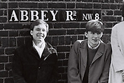 Friends standing next to Abbey Road street sign, London, UK, 1983