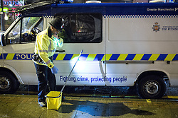 © Licensed to London News Pictures . 18/10/2013 . Manchester , UK . P.C. Dave Willetts carries the scrubbing brush and bucket full of disinfectant out of the van . Greater Manchester Police campaign against anti-social micturation . Photo credit : Joel Goodman/LNP