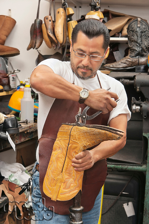 Skilled shoemaker cutting boot's sole in workshop