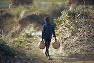 A boy carries water in calabashes for use in a nearby onion field, Dogon plateau, Mali.