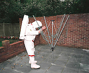 Space-suited frequent flyer astronaut Alan Watts plays moon-walker at his north London home, England. Alan, 51, runs an electrical company and qualified for a free space space flight after being contacted by Sir Richard Branson's Virgin Galactic space company, having accumulated 2 million air miles on the Virgin Atlantic flight network. Aboard the re-usable space vehicle will be 6 passengers, each of whom will have paid $200,000 for the 40 minute flight to 360,000 feet (109.73km, or 68.18 miles) and to experience just 6 minutes of weighlessness.   Flights start around 2009/10 from a Mojave desert test facility but therafter, at the new Philippe Starck-designed SpacePort America, New Mexico, USA. a 27 square mile, $225 million headquarters and mission control facility near Las Cruces.  ..