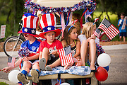 Children wearing patriotic costume ride in the back of a golf cart decorated with bunting and flags during the Daniel Island Independence Day parade July 3, 2015 in Charleston, South Carolina.