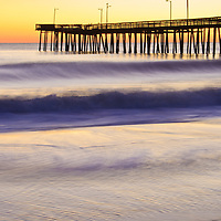 Silhoutte of the fishing pier against morning twilight and ocean waves, Virginia Beach, Virginia.