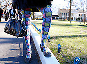 While visiting Graceland, a woman dressed in stockings that have the images of Elvis on them.