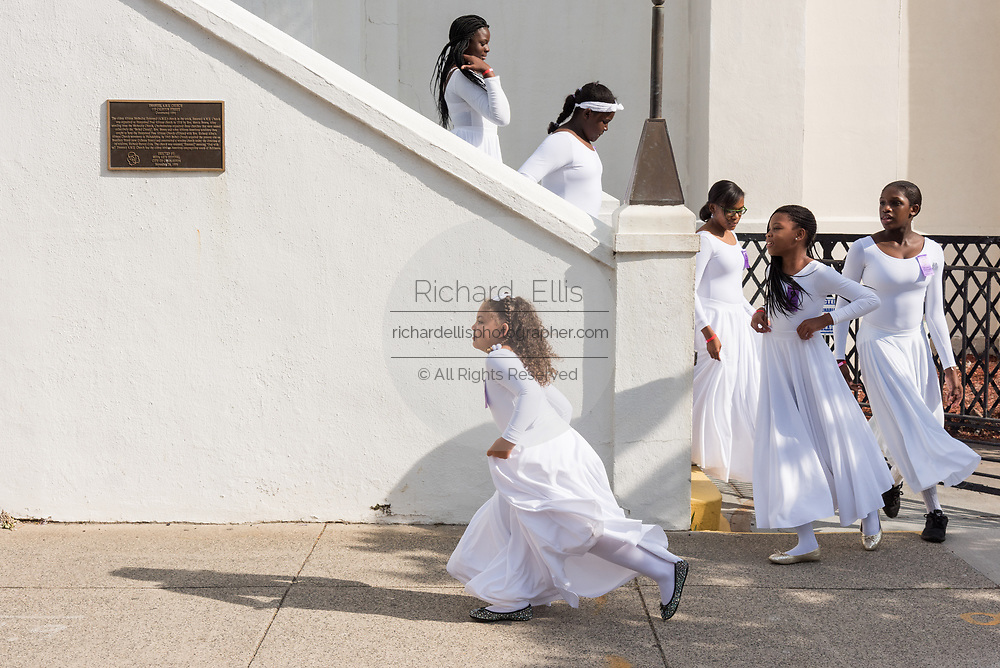 Young members of the praise dance group of the Mother Emanuel African Methodist Episcopal Church run to catch up with their group following a ceremony marking the 2nd anniversary of the mass shooting June 17, 2017 in Charleston, South Carolina. Nine members of the historic African-American church were gunned down by a white supremacist during bible study on June 17, 2015.