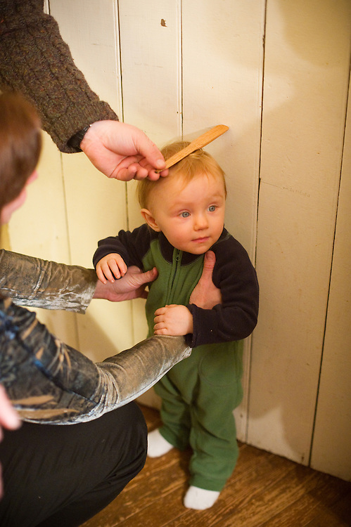 child being measured against door