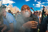 Smoking pot at the 420 Cannabis Culture Music Festival, Civic Center Park, Downtown Denver, Colorado USA. This was the first 4/20 celebration since recreational pot became legal in Colorado January 1, 2014. A crowd of up to 80,000 people attended the event.