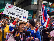 """20 DECEMBER 2013 - BANGKOK, THAILAND: An anti-government protestor on Silom Road in Bangkok. Alleged corruption by members of the Shinawatra family is one the main complaints of the protestors.  Thousands of anti-government protestors, supporters of the so called Peoples Democratic Reform Committee (PRDC), jammed the Silom area, the """"Wall Street"""" of Bangkok, Friday as a part of the ongoing protests against the caretaker government of Yingluck Shinawatra. Yingluck dissolved the Thai Parliament earlier this month and called for national elections on Feb. 2, 2014. The protestors want the elections postponed and the caretaker government to step down. The Thai election commission ruled Friday that the election would go on dispite the protests.          PHOTO BY JACK KURTZ"""
