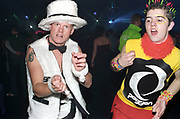 Two clubbers dancing, one wearing a furry hat and waistcoat, the other with multicolored spiky hair and colourful bracelets, Passion, Emporium, Milton Keynes, UK, 2002