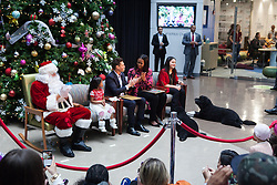 December 12, 2016 - Washington, DC, United States - On Monday, December 12, patients, families, and staff of Children's National Health System, were visited in the Main Atrium by, (l-r), Santa Claus, 5-year-old patient Abi Soliman, Ryan Seacrest, First Lady Michelle Obama, 13-year-old patient Maryam Noor Ashard, and First Dogs: Sunny, and Bo.....Mr. Seacrest, and Mrs. Obama, read the holiday classic 'Twas the Night before Christmas to the audience. (Credit Image: © Cheriss May/NurPhoto via ZUMA Press)