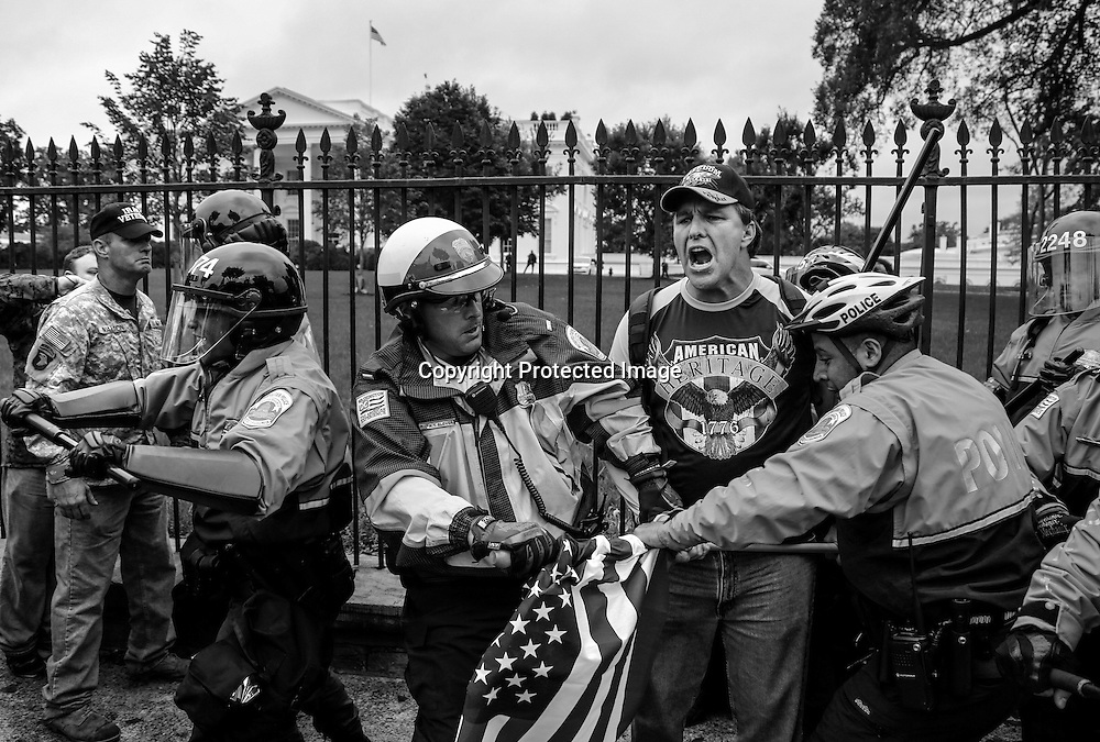 """Law enforcement officers wrestle a U.S. flag away from a man as they clash with protesters from the """"Million Vet March on the Memorials"""", rallying against the closure of the U.S. National World War Two Memorial due to the current U.S. government shutdown, as they climb the fence in front of the White House gates in Washington, October 13, 2013."""