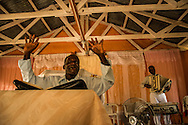 EL SEIBO, DOMINICAN REPUBLIC - OCTOBER 13, 2013: Luis Benitez, (left) sings during a Christian church service in an impoverished batey on a sugar cane plantation in El Seibo. Benitez led a Sunday church service in Creole for Haitian congregation members and their children, and led them in prayer asking God to help them to fight   judgment TC/0168, handed down by the Constitutional Court of the Dominican Republic.  The ruling essentially revokes Dominican citizenship from tens of thousands of people born in the Dominican Republic, which means they cannot have access to government services, id's necessary to travel and work, and the children cannot attend public school. The Inter-American Commission on Human Rights has expressed that the ruling would leave affected people stateless, which is a violation of the American Convention on Human Rights. During the service, the pastor discussed the idea of building a school for affected children so that they could continue their educations despite being denied birth certificates necessary for enrolling in public school.