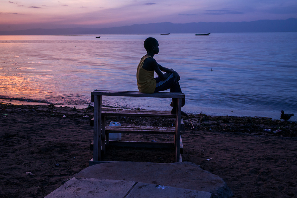 SEBAGORO, UGANDA - MARCH 22: A boy sits on the shore in Sebagoro, one of the main landing sites for refugees fleeing across Lake Albert, in Sebagoro, Uganda on March 22, 2018. Violence in Ituri Province in northeastern Democratic Republic of Congo has displaced more than 100,000 people including approximately 40,000 refugees who have fled to Uganda. (Photo by Andrew Renneisen for The Washington Post)