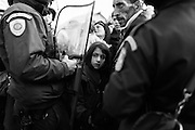 04 December 2015, Idomeni Greece - A girl in the middle of a group of refugees being pushed back by the Macedonian police.