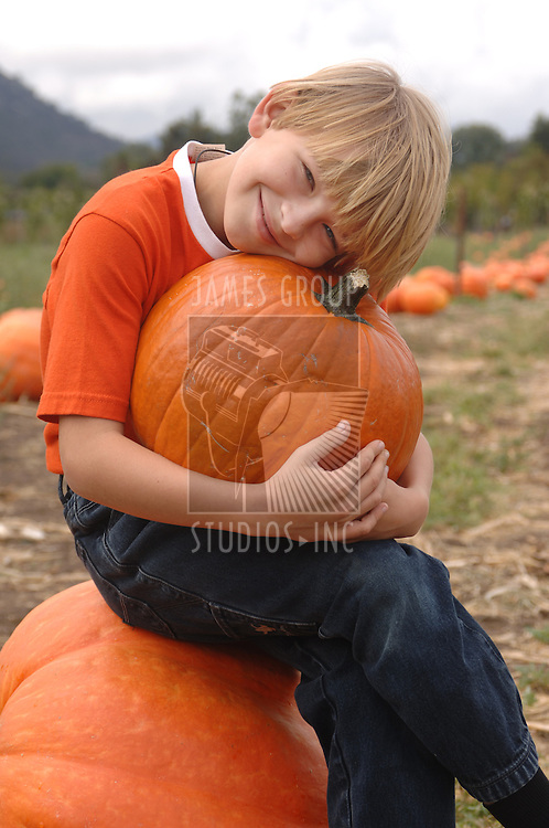 Boy holding a pumpkin found in a pumpkin patch