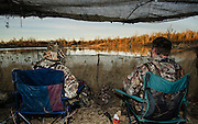 Vance Fielder (l) and Gary Friend (right) watch for ducks while hunting on a private watershed lake in Shamrock, Oklahoma