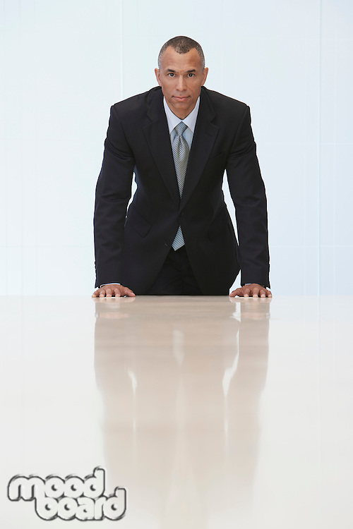 Business man standing at end of conference table portrait