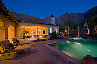 House exterior with swimming pool in backyard at dusk