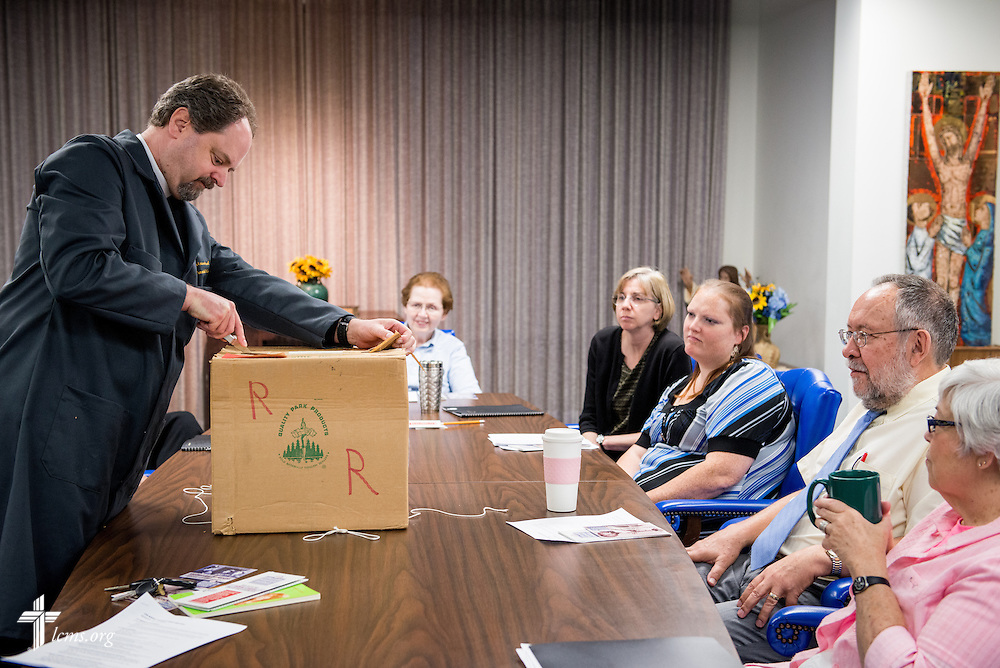 The Rev. Dr. Daniel Harmelink, executive director of Concordia Historical Institute (CHI), opens a sealed box during a short ceremony following a staff meeting Monday, July 21, 2014, in their offices on the campus of Concordia Seminary in Clayton, Mo.  LCMS Communications/Erik M. Lunsford