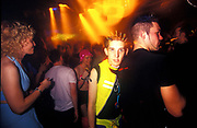 A pale raver with spikey hair wears a reflective waistcoat in a rave, London, U.K.