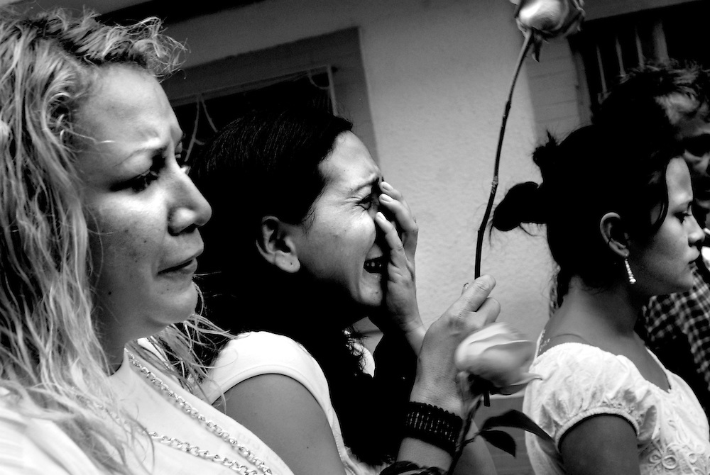 Alejandra (center) cries with her sister-in-laws, Sabrina (left) and Yomara (right) during the funeral procession for her cousin, Maximo, who was fatally shot only a few feet from the front door of Alejandra's home in Belen, a red-zone sector and notorious narco-trafficking checkpoint heavily controlled by Colombian paramilitaries. Sabrina, as well as several of Alejandra's cousins, work together as exotic dancers in the same discotec. Their boss allowed them to take several days off from work when Maximo was murdered. He was the fourth person close to the girls shot during the month of April.