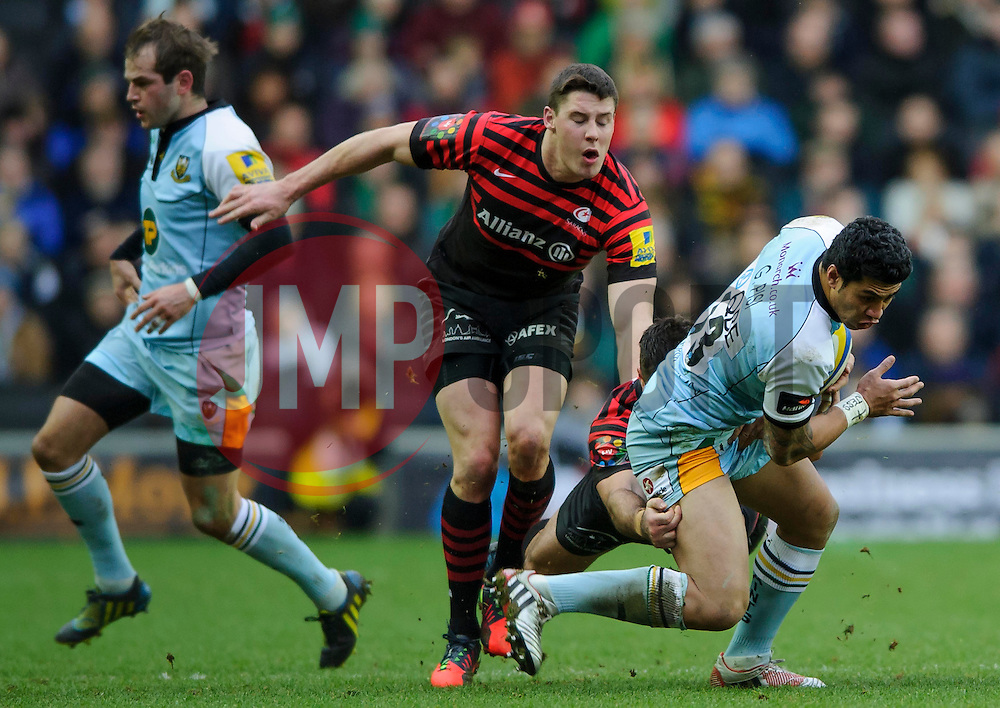 Northampton Outside Centre (#13) George Pisi is tackled by Saracens Inside Centre (#12) Brad Barritt during the first half of the match - Photo mandatory by-line: Rogan Thomson/JMP - Tel: Mobile: 07966 386802 30/12/2012 - SPORT - RUGBY - stadiummk - Milton Keynes. Saracens v Northampton Saints - Aviva Premiership.