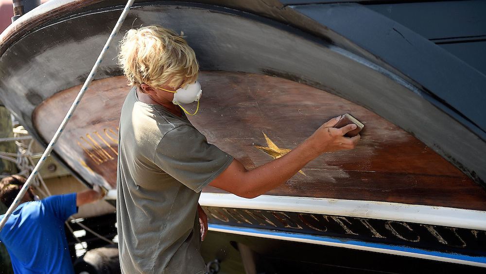 7/25/16 :: REGION :: STAND ALONE :: Sam Godfrey, right, and Joey Luketich sand the transom of the schooner Amistad docked at Mystic Seaport Monday, July 25, 2016. The schooner is in the late stages of a comprehensive refit under the auspices of the new owner, Discovering Amistad, with new sails, rebuilt engines and extensive work on the hull and rigging. (Sean D. Elliot/The Day)