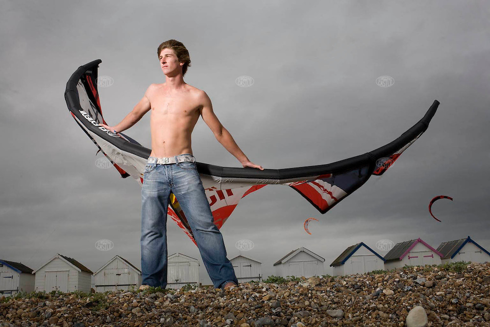 Photo ©2008 Tom Wagner,  ©Tom Wagner 2008, all rights reserved, all moral rights asserted..Portrait of Aaron Hadlow as a storm blows in at a beach near Brighton, UK, photographed June 21, 2008. Photographed with a view of the sea, and with a view of the beach huts along the shore, and with a beach pavilion. Hadlow is 19 years old and is 4 times PKRA World Kitesurfing Champion, having won his first World Championship when just 15 year old. Hadlow is British and lives in the UK. He has been unbeaten in Freestyle Kiting since 2004, according to Redbull website, one of his sponsors.