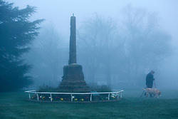"© Licensed to London News Pictures. 14/03/2014. Meriden, Coventry, UK. Dense fog covered the Midlands earlier today. A man and his dog walk past the ""Centre of England"" monument in Meriden, near Coventry. Photo credit : Dave Warren/LNP"